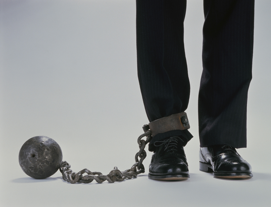 Man with ball and chain attached to leg