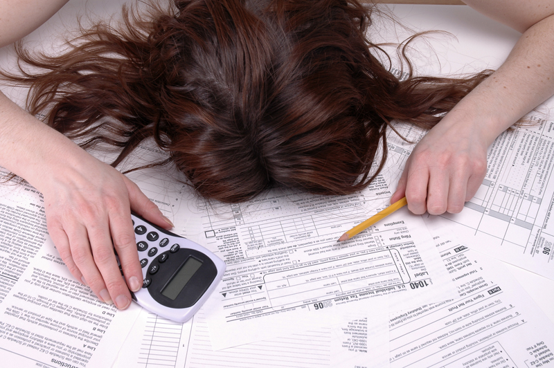 Woman at desk with head down on tax forms, holding a pencil and calculator.