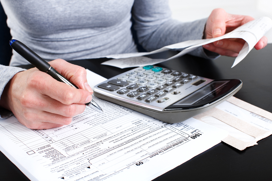 Woman looking at receipts with calculator and 1040 tax forms on desk