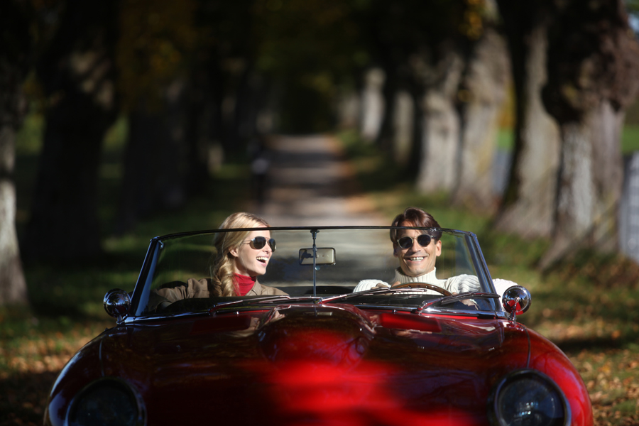 Man and Woman riding in a red car