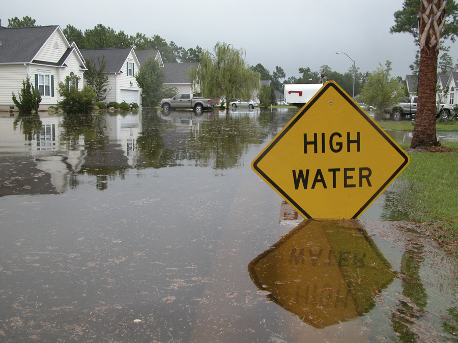 Flooded street with sign that says High Water