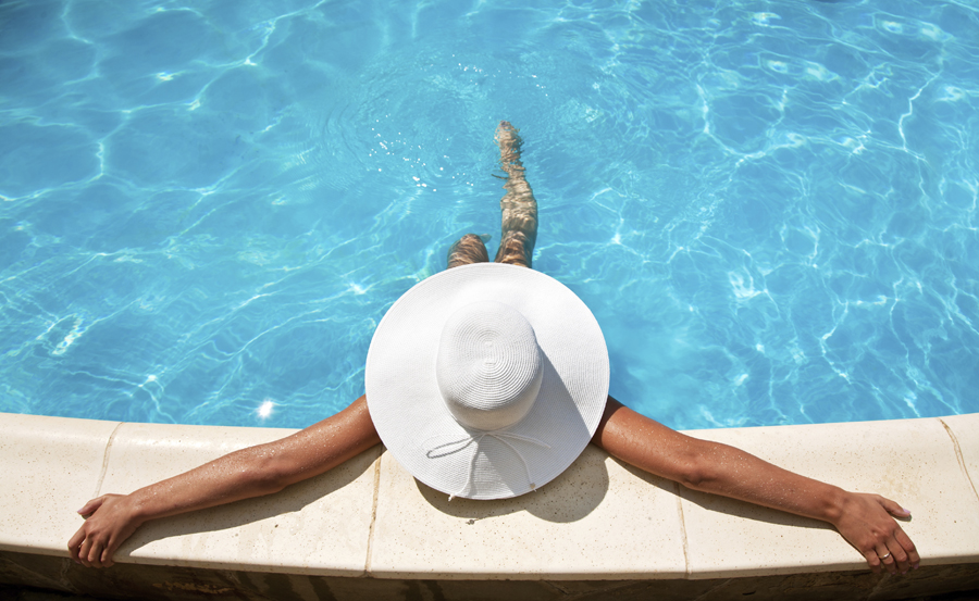 Woman in white hat in a swimming pool