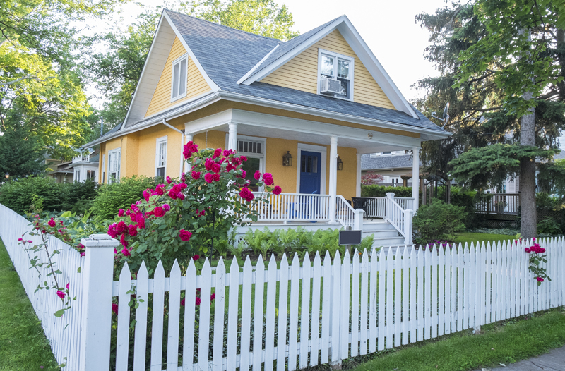 Yellow house with white fence
