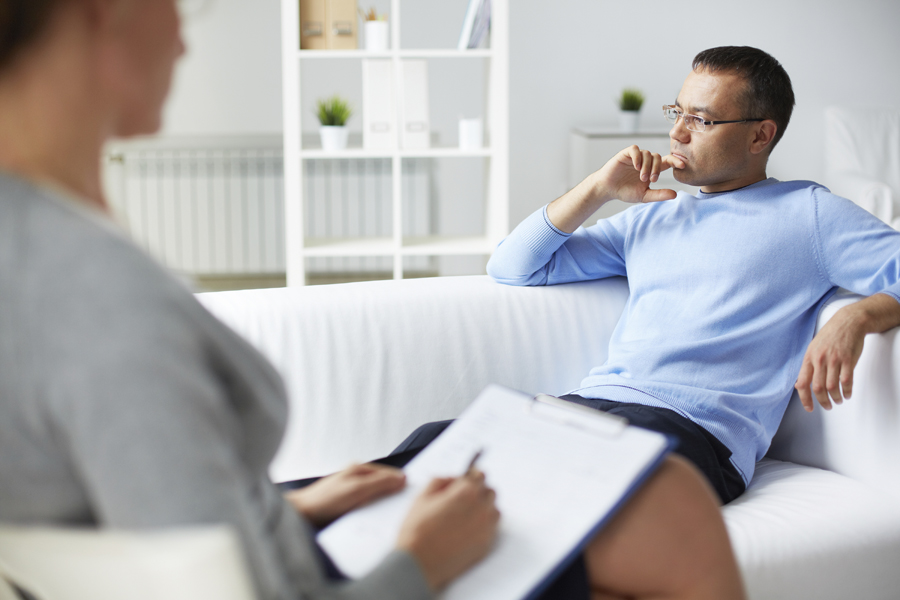 Man on couch talking to Psychotherapist