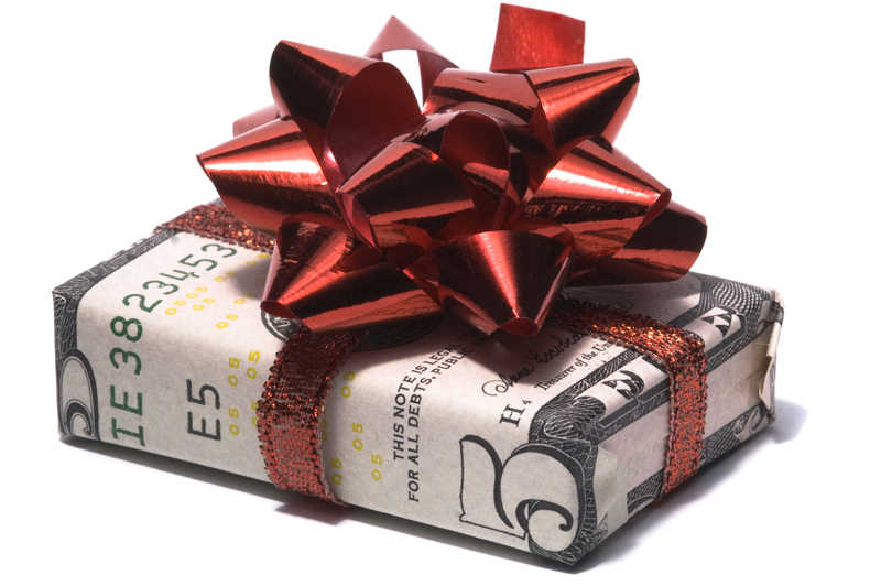 Gift box wrapped in a five dollar bill with a red ribbon and bow on top