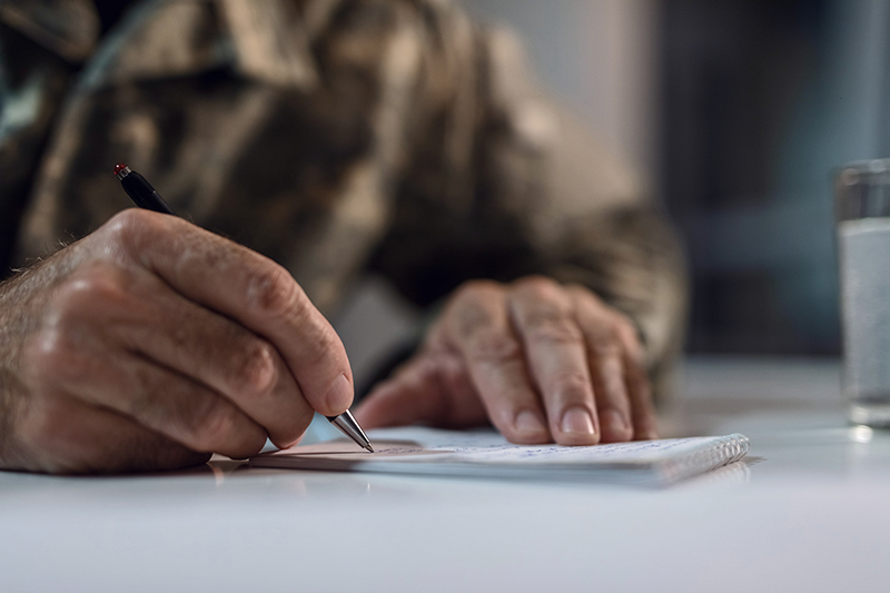 Armed Forces member writing on a notepad