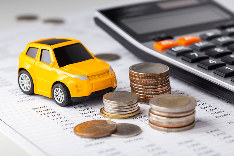 car, money, and calculator on financial sheet
