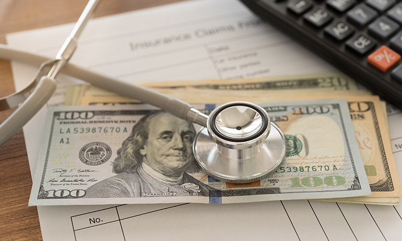 stethoscope on top of stack of cash over an Insurance Claims statement