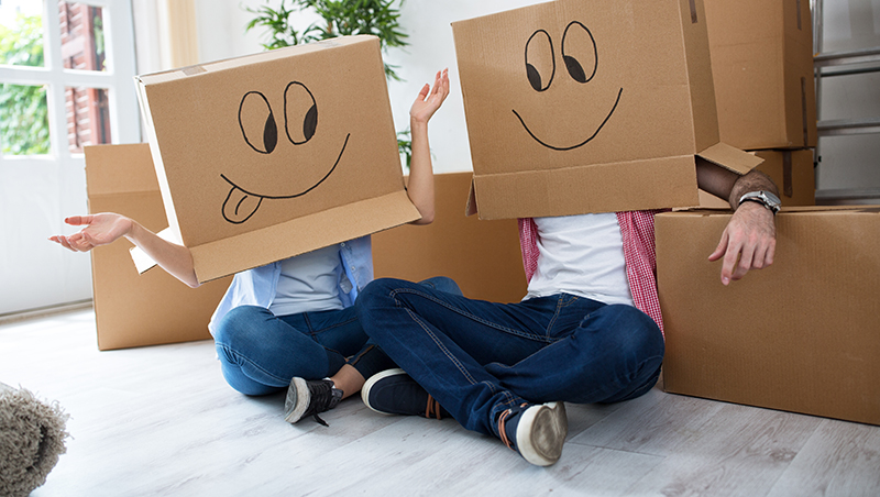 Couple with moving boxes on their heads with happy faces drawn on them