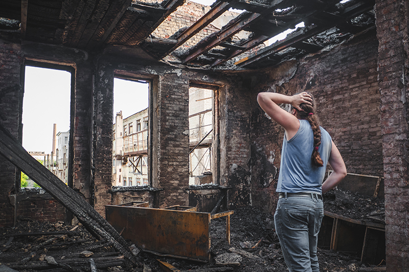 woman looking at home after disaster