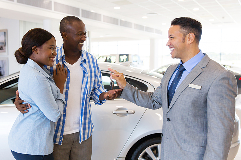 Couple receiving keys from salesman to their new car
