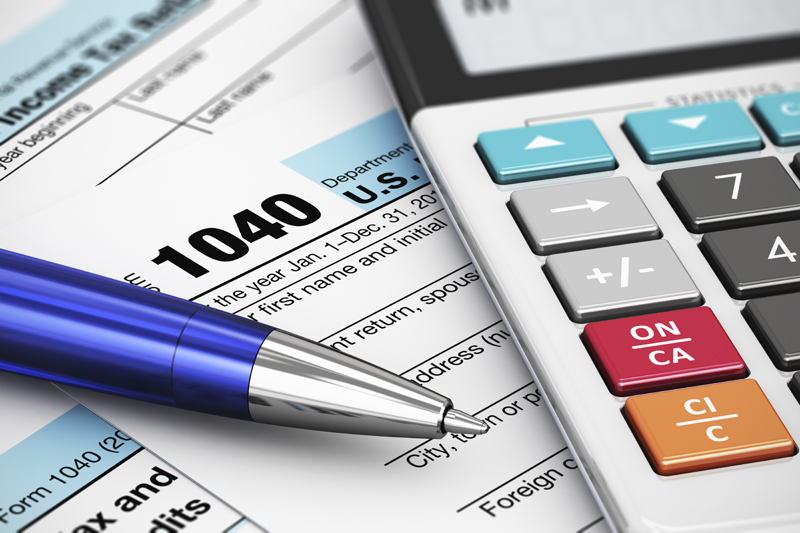 Calculator and pen on top of 1040 tax forms