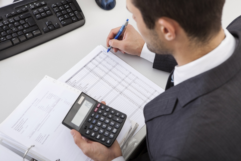 Man working at desk holding a calculator
