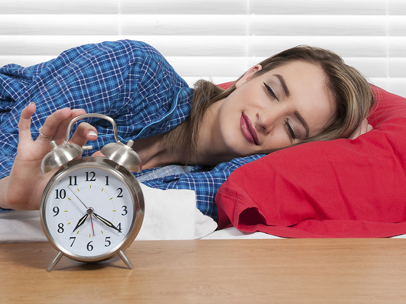 woman hitting the snooze button on alarm