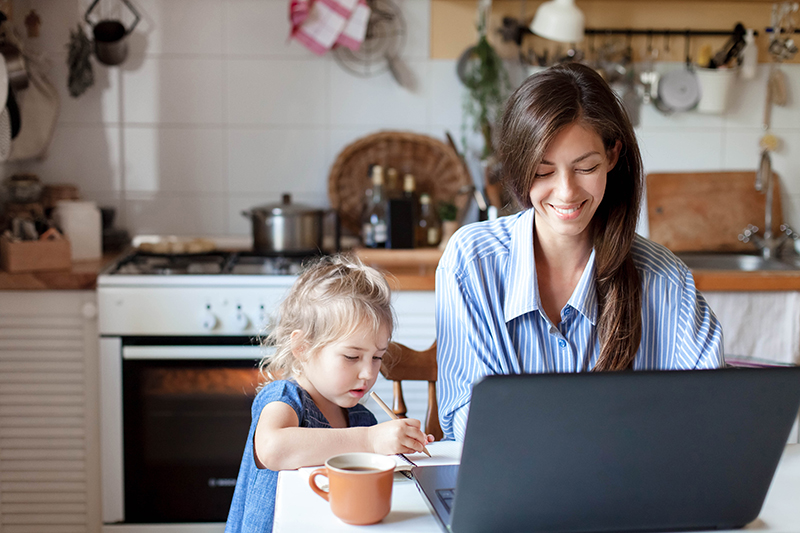 Woman working from home with child next to her