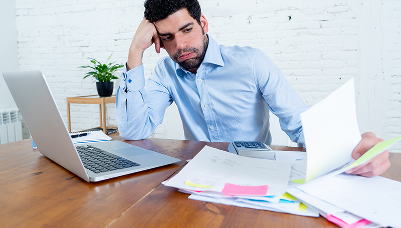 distressed business owner looking at paperwork