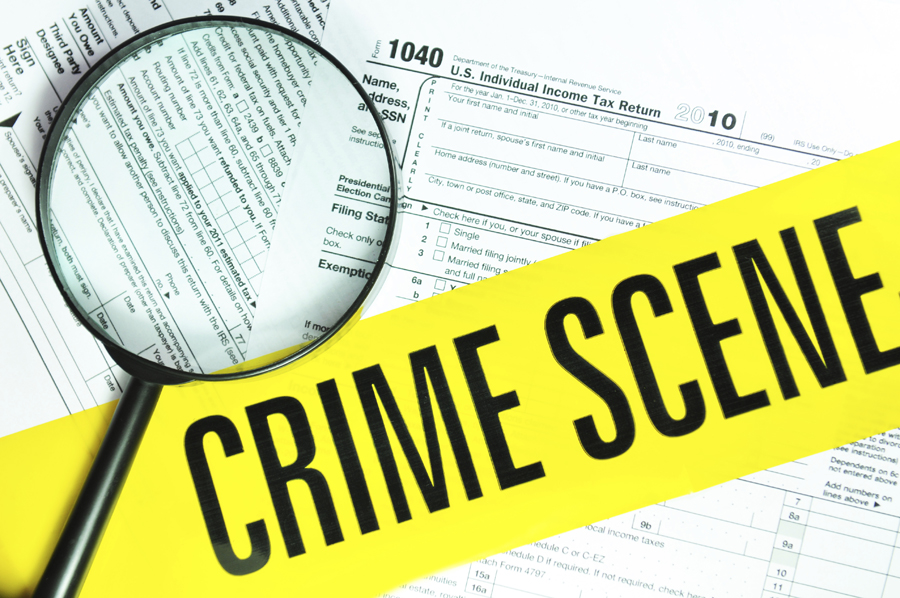 Magnifying glass over tax forms with crime scene tape