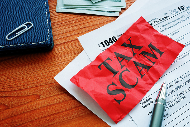 Tax Scam written on red paper over tax return