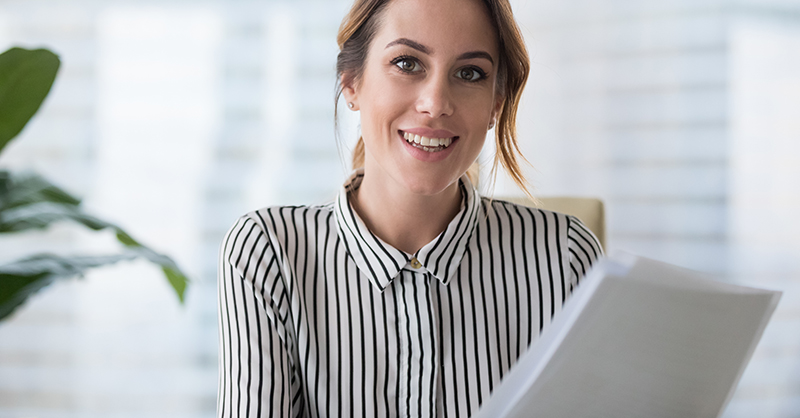 woman smiling while holding paperwork