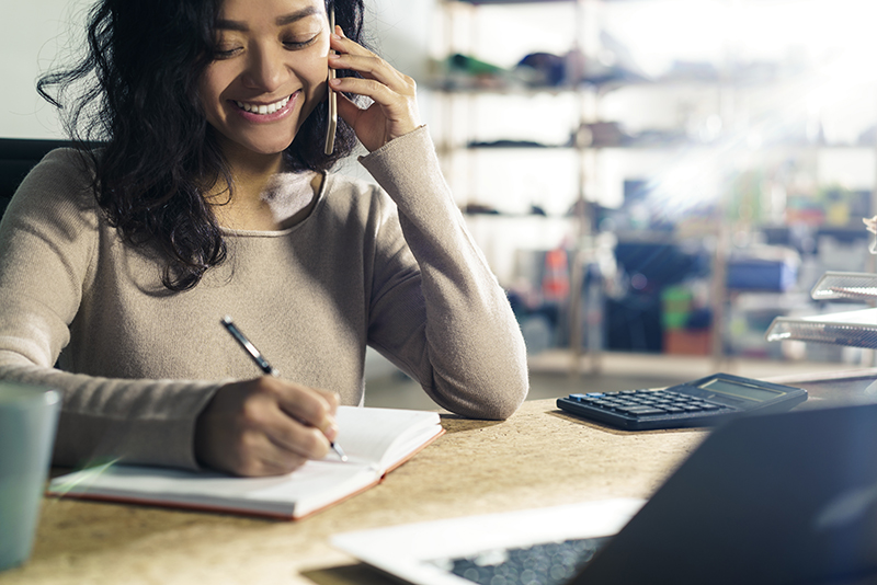 Woman smiling while talking on the phone and taking notes