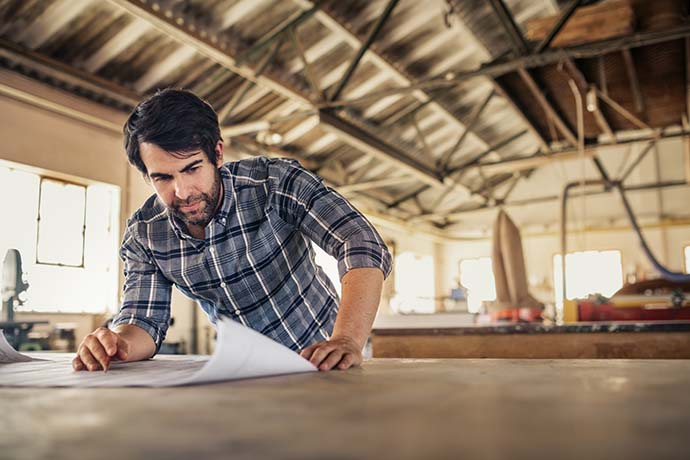 Self-employed man looking at plans