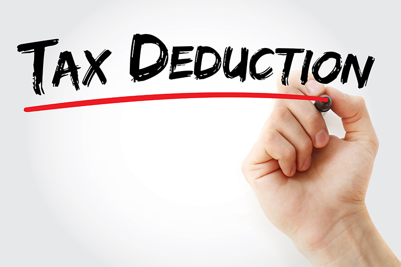 Hand with pen writing Tax Deduction