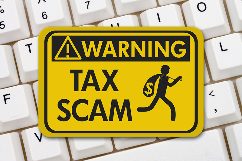 Warning tax scam sign laying on a keyboard