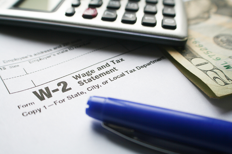 W-2 tax form next to a pen, money, and calculator