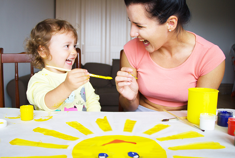 babysitter painting a sun with a child
