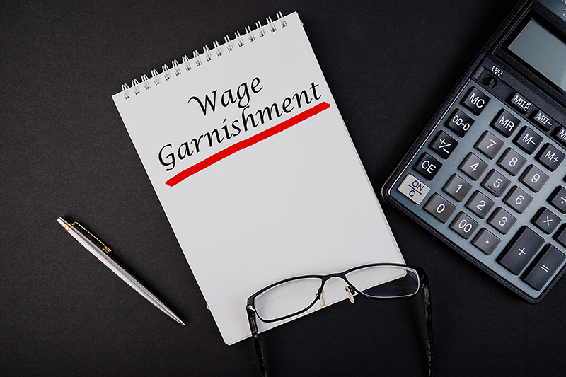 Wage Garnishment written on paper next to calculator