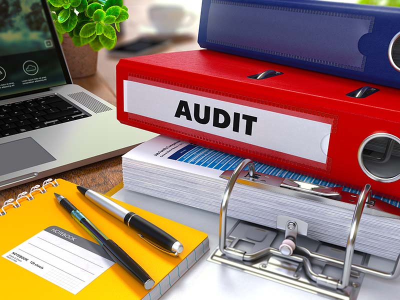 red binder labeled audit