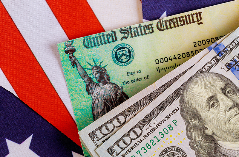American Flag with United States Treasury check and two $100 bills