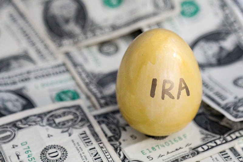 Golden IRA egg sitting on money