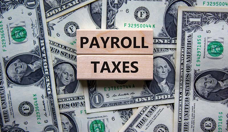 Payroll Taxes Sign on top of dollar bills